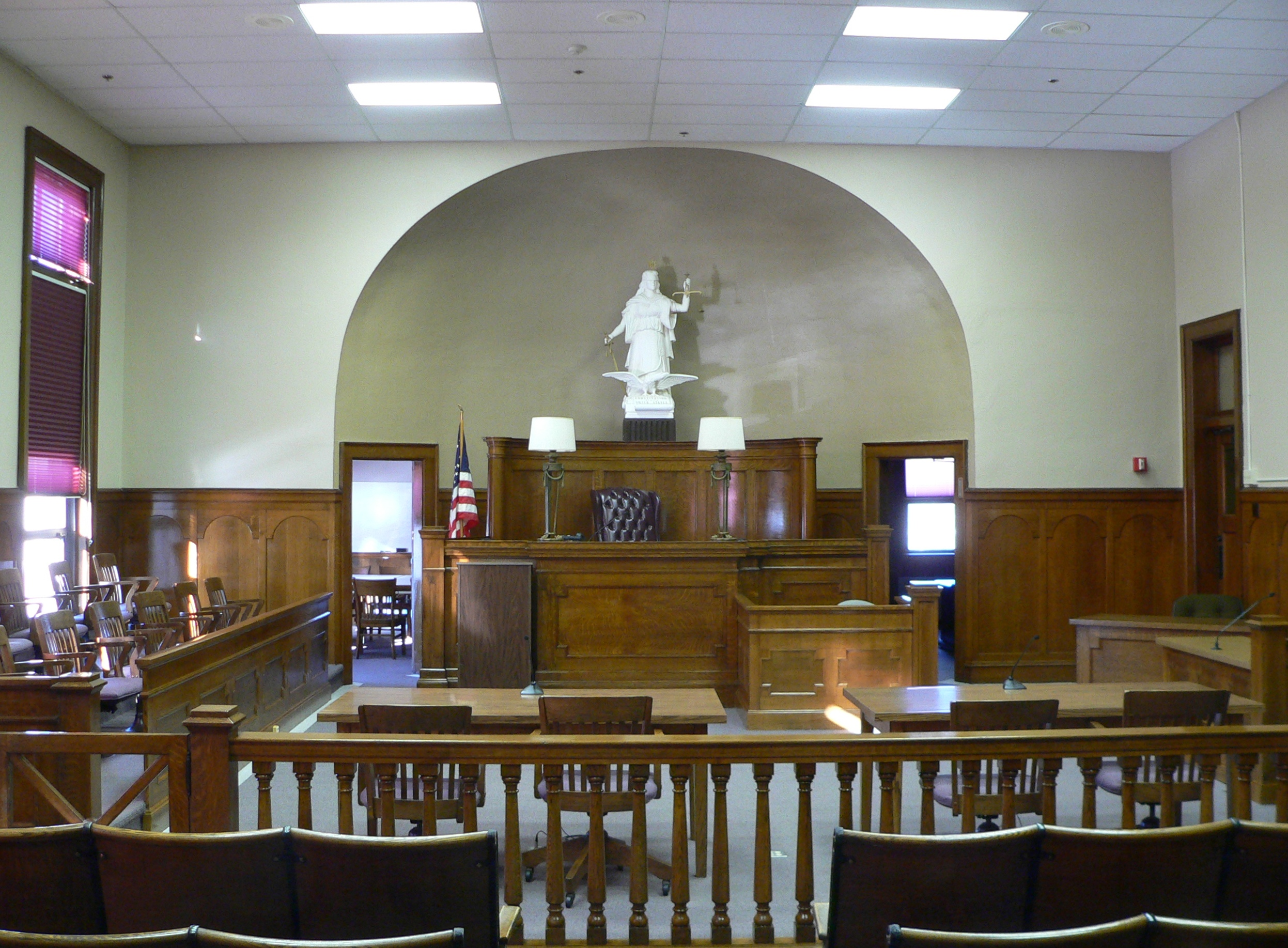 court room A courtroom is the enclosed space in which courts of law are held in front of a judge a number of courtrooms, which may also be known as courts, may be housed in a courthouse the judge generally sits behind a raised desk, known as the bench.